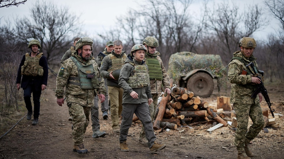 President Zelensky, surrounded by soldiers, wears protective clothing.