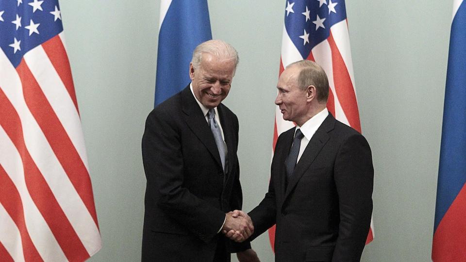 Joe Biden and Vladimir Putin shake hands.