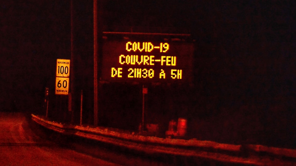 An illuminated sign indicates curfew hours on the highway.