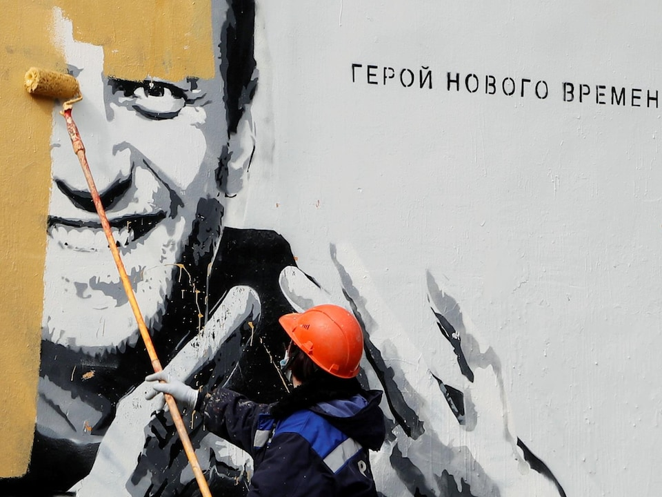 A worker paints on a pro-Navy mural in Russia.