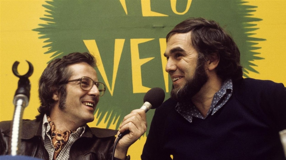 Pierre Paquette hands over a microphone to a smiling Claude Jasmine.