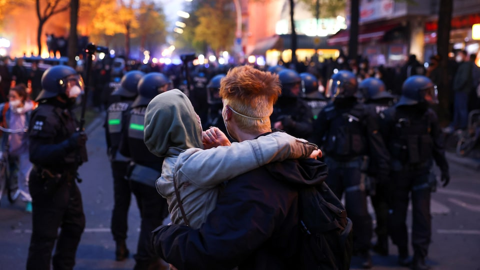 A couple embrace in front of the police and the protesters.