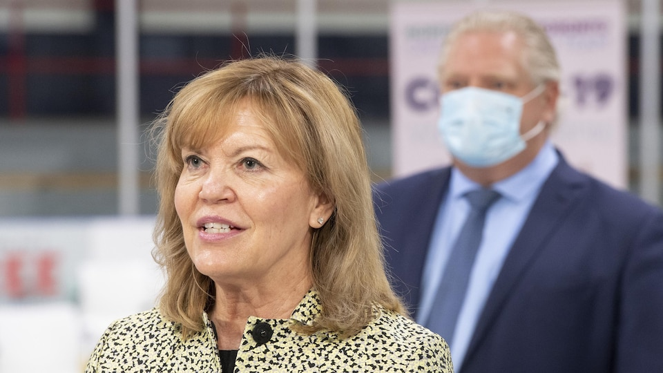 Ontario Health Minister Christine Elliott speaks during a press conference in a yard that has been converted into a vaccination center.