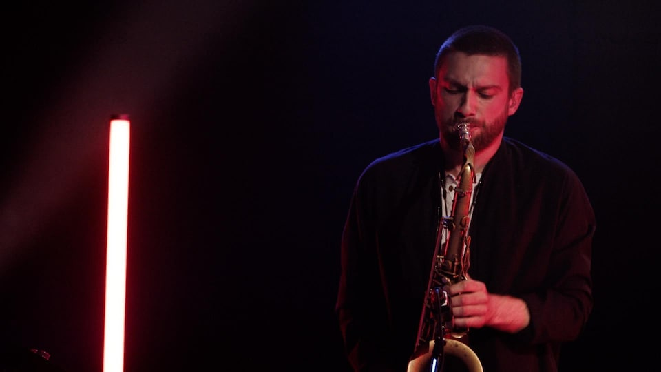 The artist plays the saxophone on a dimly lit stage.