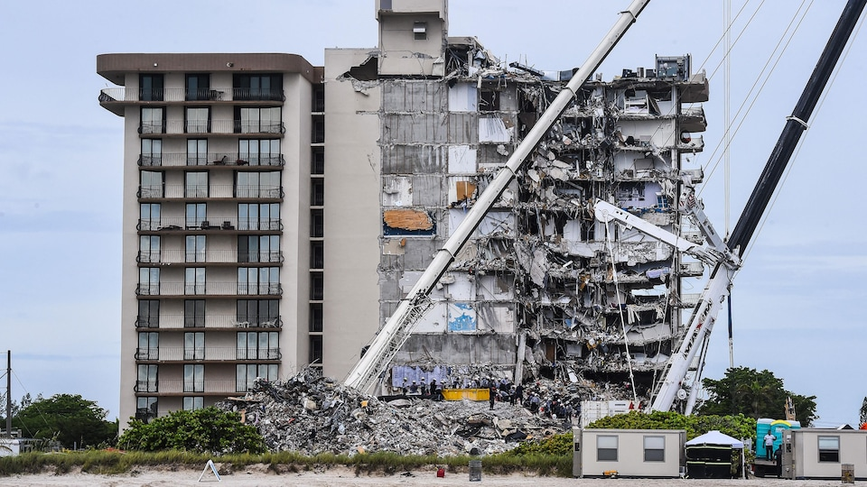 Two cranes appear in front of the building, one side of which is torn and partially destroyed.