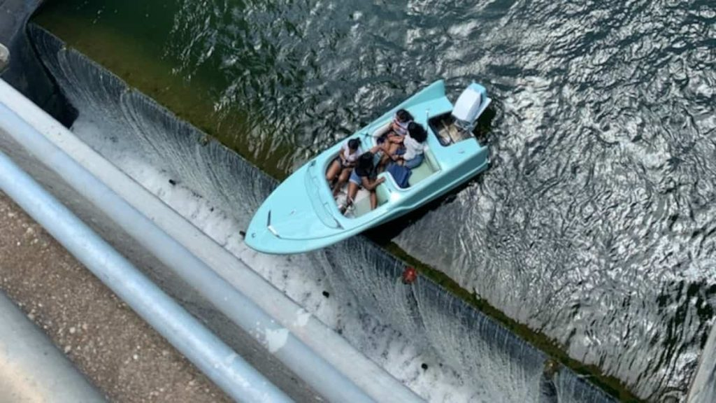 in pictures |  Their boat shakes dangerously at the edge of the dam