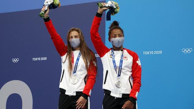 Mélissa Citrini-Beaulieu et Jennifer Abel célèbrent leur médaille d'argent au cou, le bras droit au ciel et un bouquet à la main, sur la deuxième marche du podium.