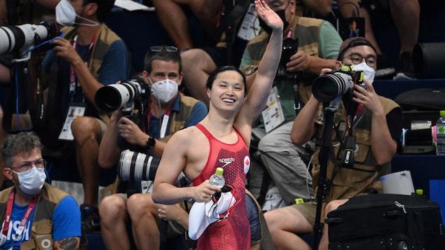Une jeune femme s'asperge d'eau dans une piscine. Elle va nager dans une compétition olympique.