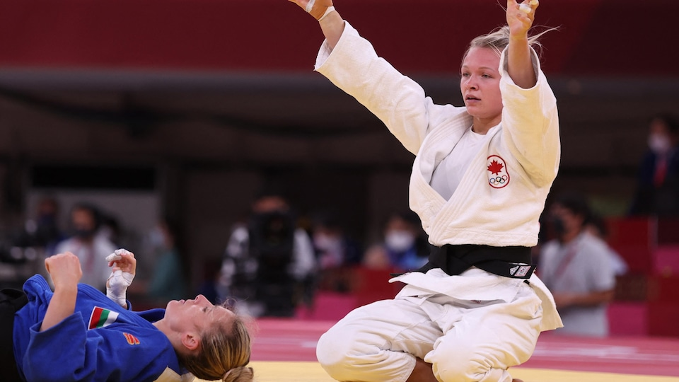 Kneeling, the Canadian judoka raises her arms to the sky while her Bulgarian opponent lies on the ground next to her.