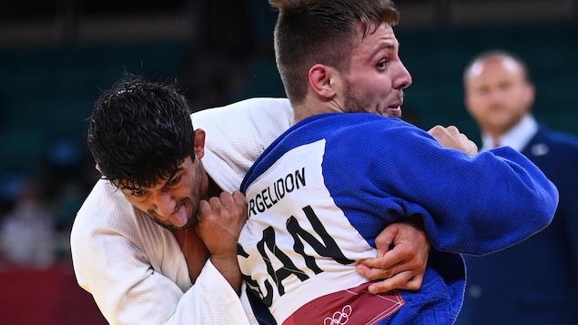 Lasha Shavdatoashvili (in a white kimono) and Arthur Marglidon held on to them during their quarter-final fight.