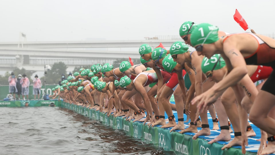 Athletes at the water's edge to start the triathlon.