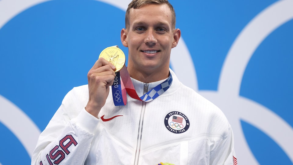 An American athlete wearing a USA-colored coat proudly displays his gold medal.