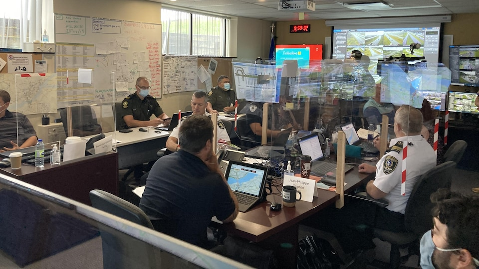 Several people gathered in a room.  Screens display images from traffic cameras.