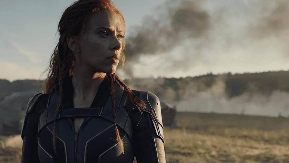 A woman in a superhero costume watches the horizon.  A plume of black smoke appears in the background.