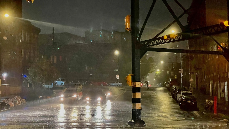 Vehicles drive on a flooded New York street at night.