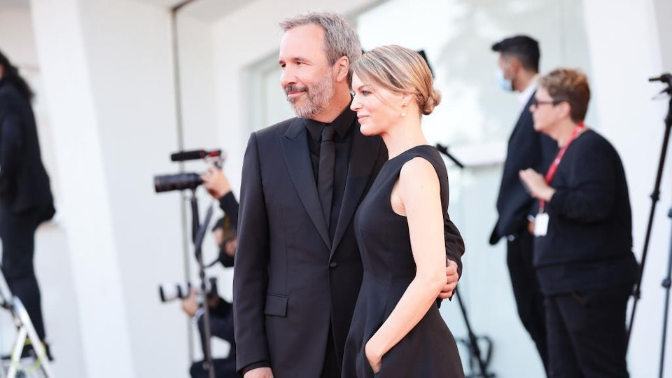 A woman and a man dressed in black pose in front of the photographers.