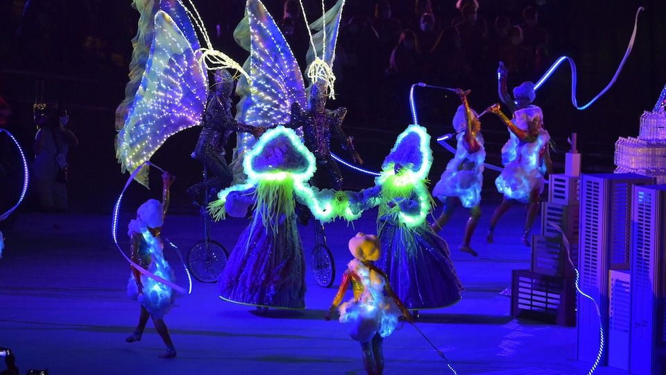 Artists dance and perform routines in luminous costumes.