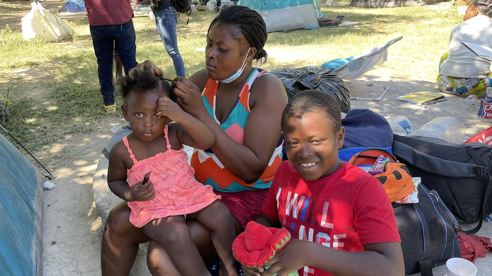 A mother combs her daughter's hair.