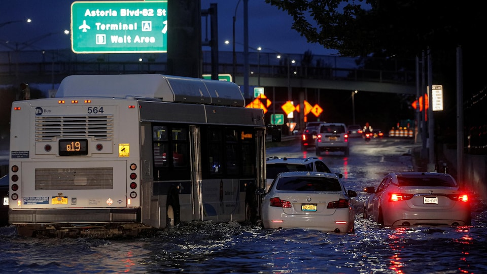 A bus passes near abandoned cars on a flooded highway in Queens, New York.