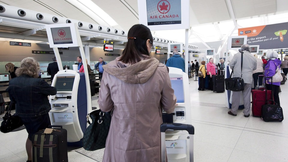 Passengers check in at one of the kiosks.