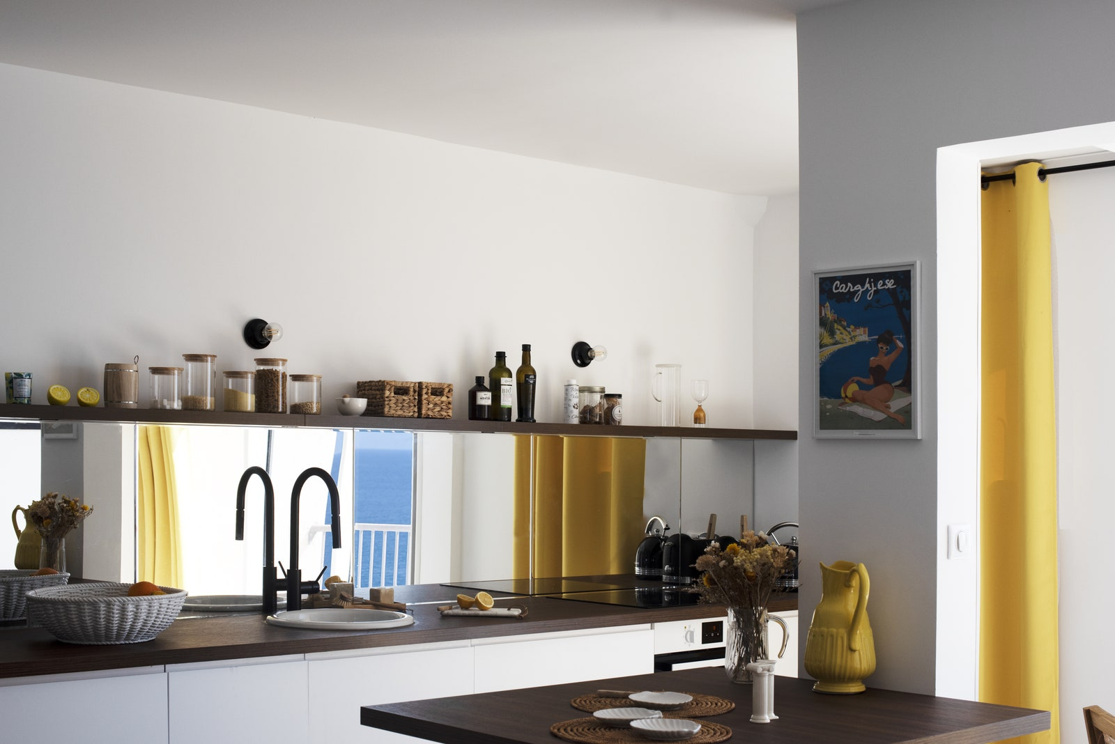 White base units covered in a mirrored credenza occupies the entire kitchen wall.  Worktop and shelf...