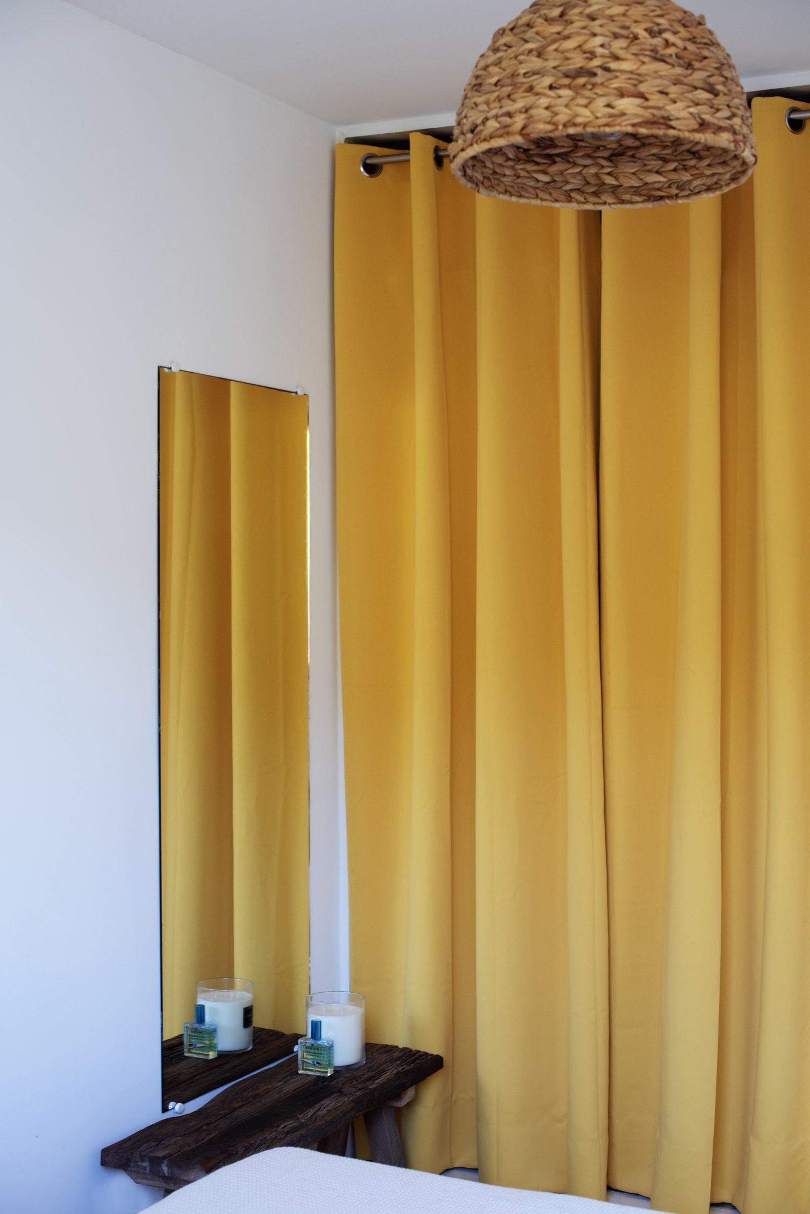 In the bedroom, raw simplicity is awakened by large yellow curtains and a woven straw pendant light.