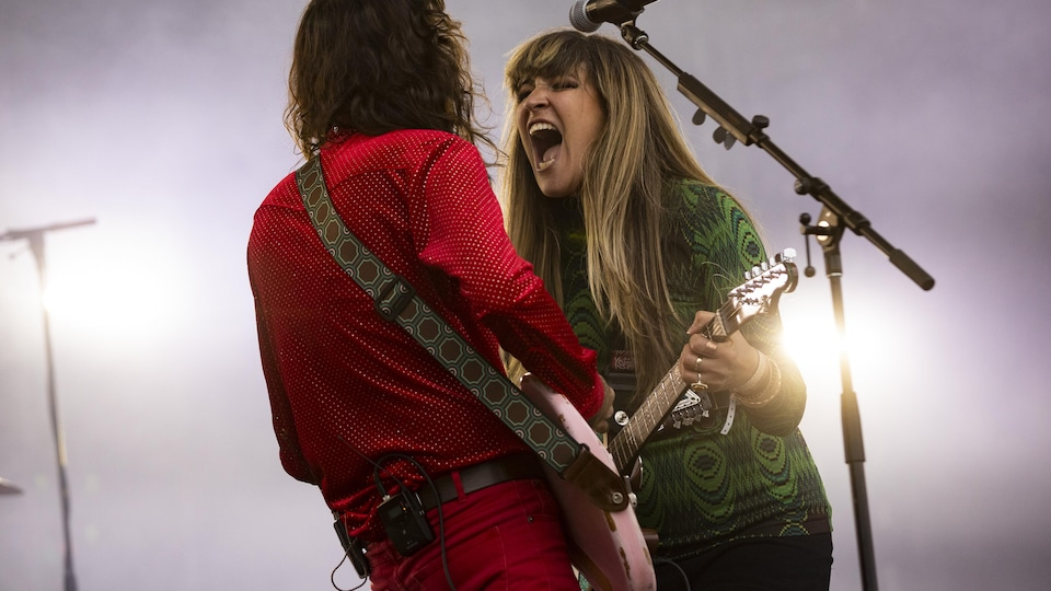 Two guitarists playing on stage looking at each other.