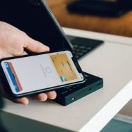 An individual pays for a service or product using the Apple Pay app available on his iPhone.